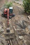 开掘坑的红色挖掘机 免版税图库摄影