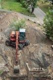 开掘坑的红色挖掘机 免版税库存图片