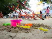 开掘它的沙子的玩具有在沙子放置的一种美好的颜色 背景是操场 有孩子和成人 免版税图库摄影