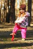 开掘森林的小孩女孩的画象研了与玩具红色铁锹 图库摄影