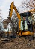 开掘沟槽的微型挖掘机在城市通信下 免版税图库摄影