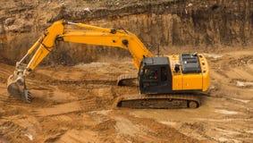 开掘沟槽的运转的挖掘机拖拉机 库存图片