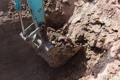 开掘沟槽的运转的挖掘机拖拉机 免版税库存照片