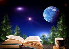 开放书和一杯咖啡在夜空的背景的 免版税库存图片