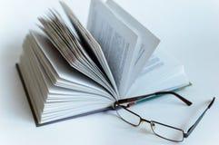 开放书在隔离的白色背景说谎在白色背景 玻璃 免版税图库摄影