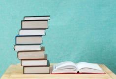 开放书,堆精装书在木桌上预定 库存照片