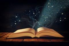 开放古色古香的书的图象在木桌上的与闪烁覆盖物 免版税库存图片