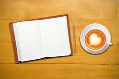 开放咖啡杯的笔记本 免版税库存图片
