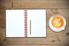 开放咖啡杯的笔记本 库存图片