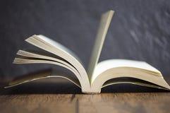 开放在图书馆教育概念的书葡萄酒老木桌黑暗的背景 免版税库存照片