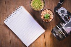 开放在木桌上的笔记本和照相机的顶视图图象有空白页和两仙人掌的 免版税库存图片