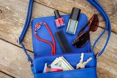 从开放夫人钱包的事 化妆用品、金钱和妇女` s辅助部件落在蓝色提包外面 库存图片