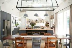 开放学制厨房吃饭的客人在期间转换房子 免版税库存图片