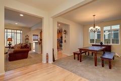 开放学制的楼层 餐厅看法有被雕刻的木桌、客厅和厨房的 免版税图库摄影