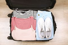 开放手提箱充分堆积用不同的衣裳 库存图片
