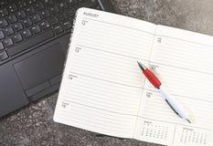 开放日历或计划者和笔在手提电脑 图库摄影