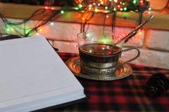 开放日志,透明茶在钢杯座的在一本灼烧的壁炉和圣诞节诗歌选的背景 免版税库存照片
