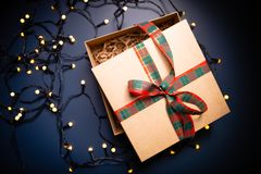 开放有丝带的纸盒当前箱子在装饰光围拢的蓝色背景 免版税库存照片