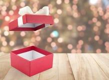 开放的特写镜头和有白色丝带弓的空的红色礼物盒在与defocused小五颜六色的光的葡萄酒褐色木台式 免版税库存照片