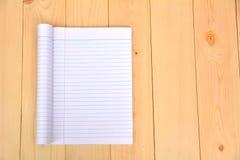 开放的笔记本显示在木的白皮书 图库摄影