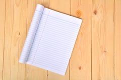 开放的笔记本显示在木背景的白皮书 免版税图库摄影