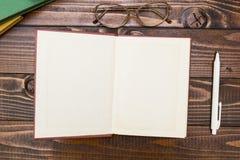 开放空白的书、笔和玻璃在一张木桌上 在视图之上 文本的空间 库存图片