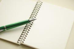 开放空白的白色笔记本和绿色笔的部分在书桌上 免版税图库摄影