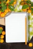 开放空白的围拢的圆环一定的笔记本演播室摄影新鲜水果李子和铅笔在黑暗的木桌上 免版税库存图片