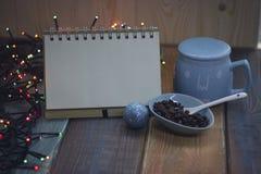 开放笔记本、蓝色杯子和咖啡豆在圣诞节tablen 免版税库存照片