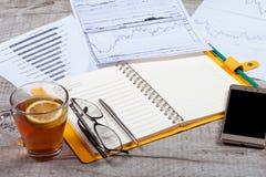 开放笔记本、玻璃、一杯茶,笔和智能手机顶视图在一张木桌上 免版税图库摄影