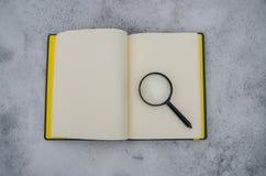 开放笔记本和放大镜在白雪背景  免版税图库摄影