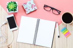 开放笔记本的顶视图图象有空白页、辅助部件和咖啡杯的在木背景,为增加准备或嘲笑  免版税库存照片