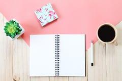开放笔记本的顶视图图象有空白页、辅助部件和咖啡杯的在木背景,为增加准备或嘲笑  库存图片