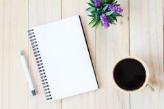 开放笔记本的顶视图图象有空白页和咖啡杯的在木背景,为增加准备或嘲笑  免版税库存照片