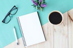 开放笔记本的顶视图图象有空白页和咖啡杯的在木背景,为增加准备或嘲笑  免版税库存图片