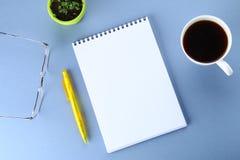 开放笔记本的顶视图图象有空白页和咖啡的在蓝色背景,为增加准备或嘲笑  静物画,事务, 免版税库存照片