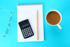 开放笔记本的顶视图图象有空白页和咖啡的在蓝色背景,为增加准备或嘲笑  静物画,事务, 免版税图库摄影