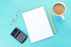 开放笔记本的顶视图图象有空白页和咖啡的在蓝色背景,为增加准备或嘲笑  静物画,事务, 免版税库存图片