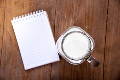 开放笔记本的顶视图图象有空白页和牛奶的在水罐和玻璃 免版税库存照片