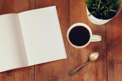 开放笔记本的顶视图图象有空白页的在杯子在木桌上的coffe旁边 为增加文本或大模型准备 免版税图库摄影