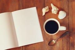 开放笔记本的顶视图图象有空白页的在杯子在木桌上的coffe旁边 为增加文本或大模型准备 库存照片