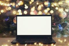 开放膝上型计算机的图象有白色屏幕的在圣诞树背景前面的木桌上 库存照片