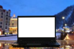 开放膝上型计算机的图象有白色屏幕的在圣诞节冬天风景前面的木桌上点燃背景 免版税库存图片