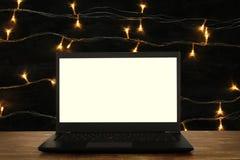 开放膝上型计算机的图象有白色屏幕的在抽象闪烁背景前面的木桌上 对大模型 免版税图库摄影