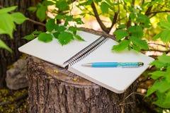 开放螺旋空白的笔记薄顶视图与笔的在木树桩背景和绿色在分支离开 库存照片