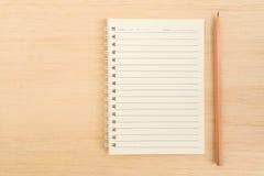 开放螺旋线纸笔记本和棕色铅笔顶视图  库存图片