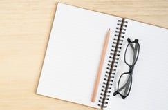 开放螺纹笔记本顶视图有棕色铅笔和黑眼睛的 库存图片