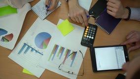 开无法认出的年轻创造性的起始的队看打印的数据和分析图表的进展会议 股票录像