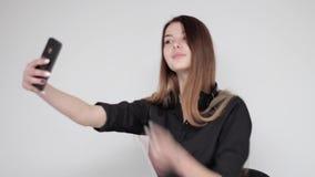 离开无线耳机的悦目女孩摆在为selfie照片 股票视频