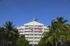 开曼群岛、美国和得克萨斯州在位于七英里的豪华旅游胜地前面的旗子靠岸 免版税图库摄影